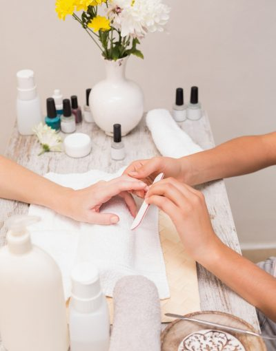 Nail technician giving customer a manicure at the beauty salon